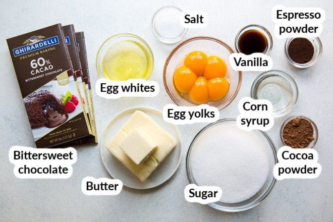 Labeled flourless chocolate cake ingredients in various bowls.