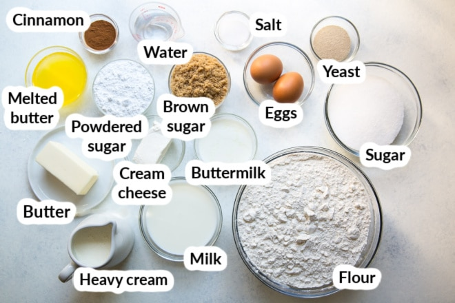 Labeled cinnamon roll ingredients in various bowls.