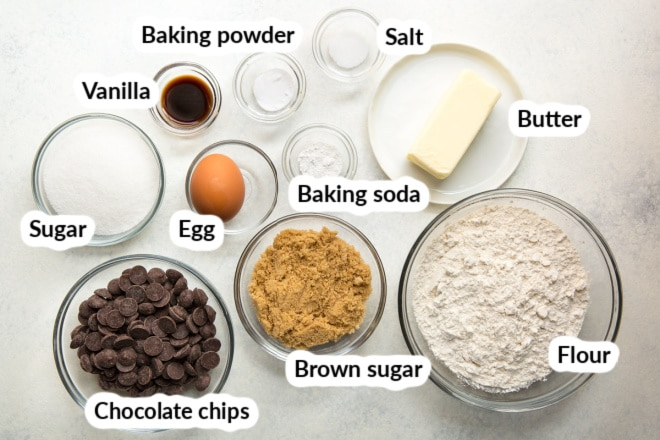 The ingredients for chocolate chip cookies arranged in bowls and labeled.