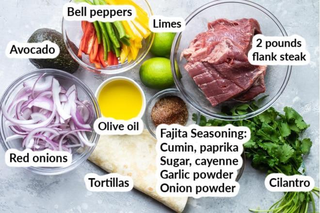 Steak fajita ingredients in various bowls and labeled.