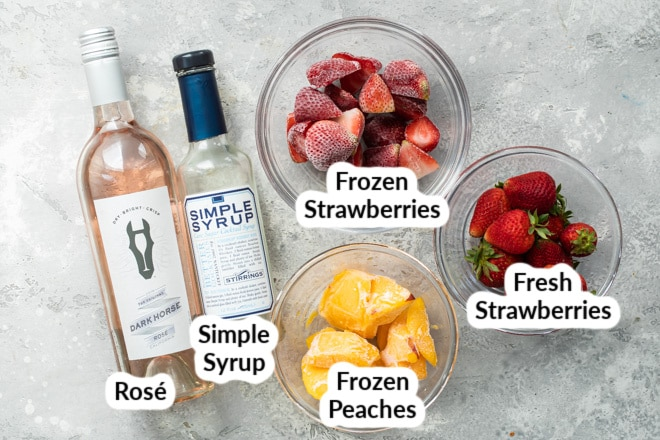 Strawberry peach frosé ingredients on a gray countertop.