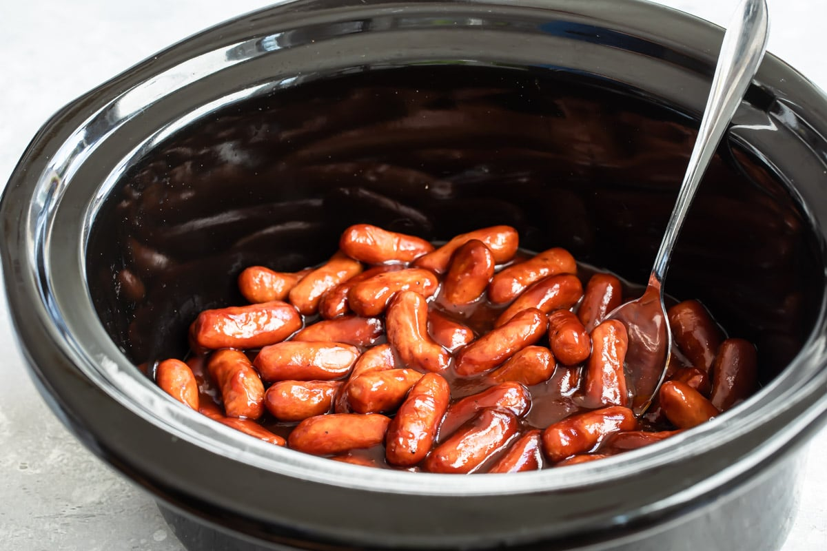 Barbecue little smokies being cooked in a crockpot.