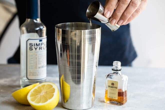 Amaretto sour ingredients being added to a martini shaker.