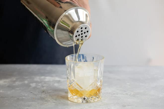 Amaretto sour being poured into a glass.
