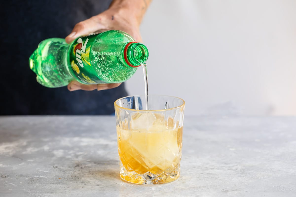Lemon-lime soda being poured over an amaretto sour.