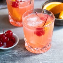 A brandy old fashioned in a clear glass.