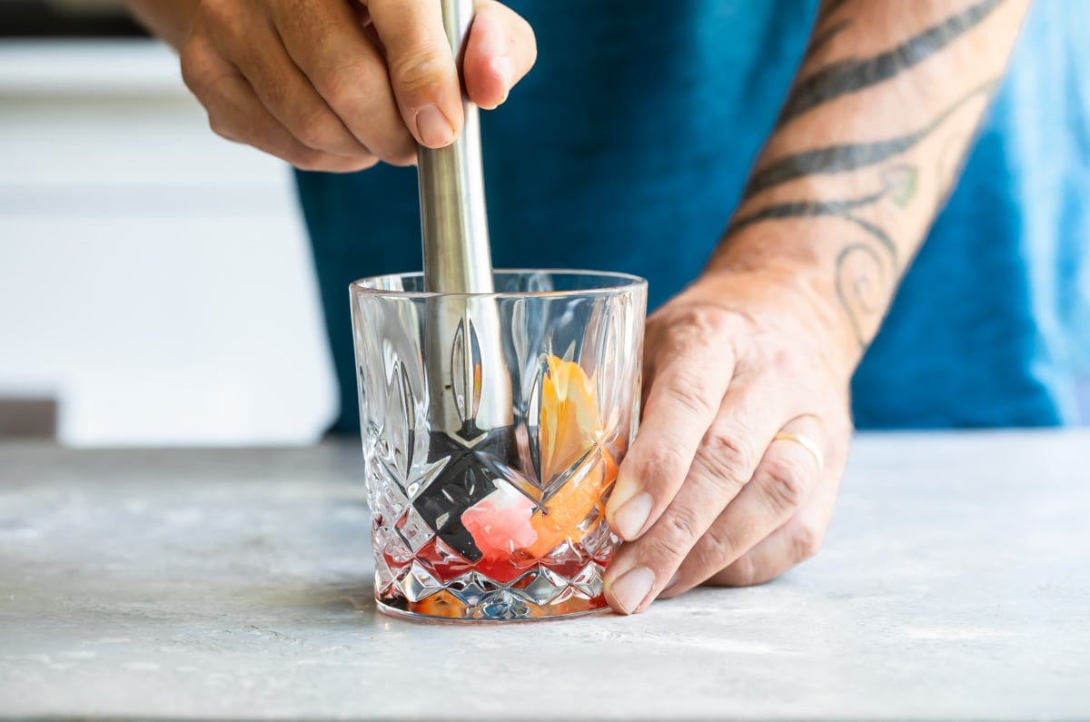 Old fashioned ingredients being muddled in a clear glass.
