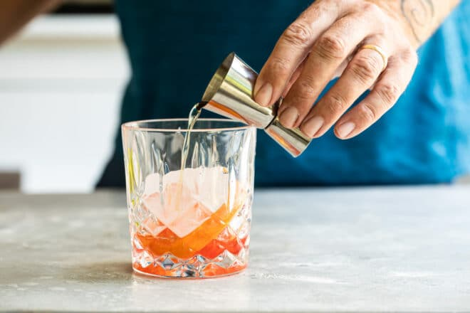 Brandy being poured into a clear glass with ice and red liquid in the bottom.