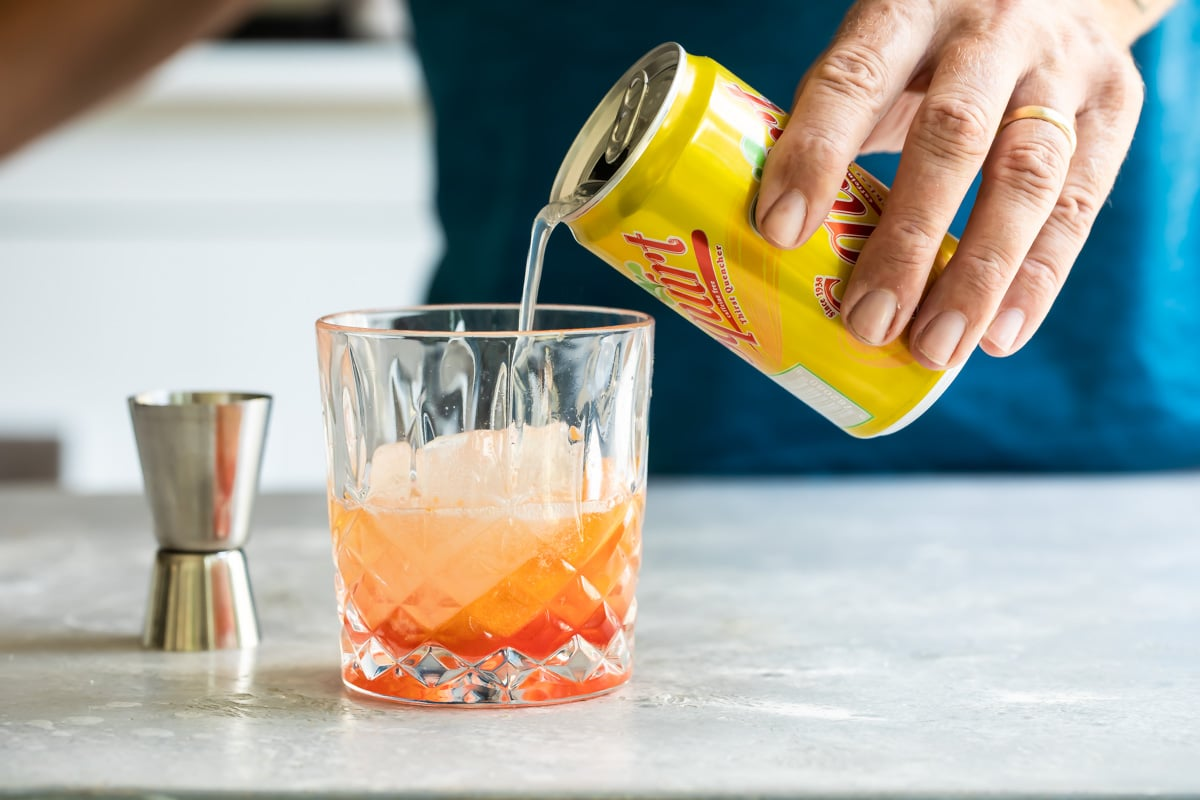 Soda being poured into a Brandy Old Fashioned cocktail.