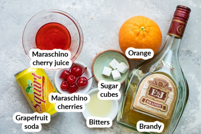 Labeled brandy old fashioned ingredients in bowls and bottles.