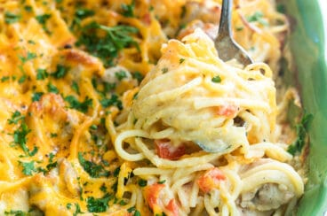 Chicken spaghetti being scooped out of a green casserole dish.