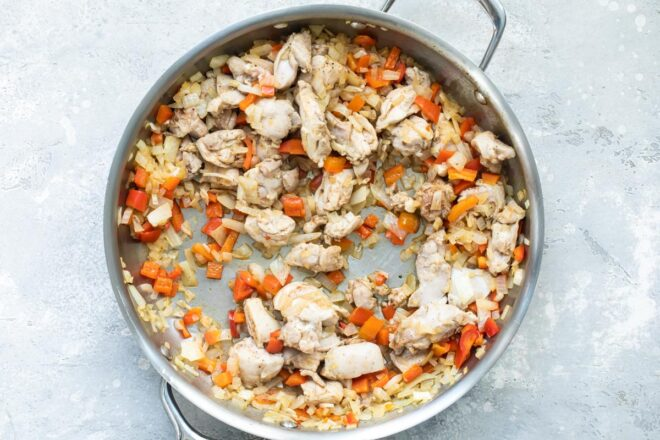 Chicken chunks and vegetables in a silver pan.