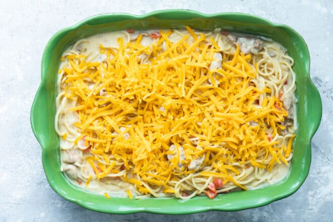Chicken spaghetti in a green baking dish before being baked.