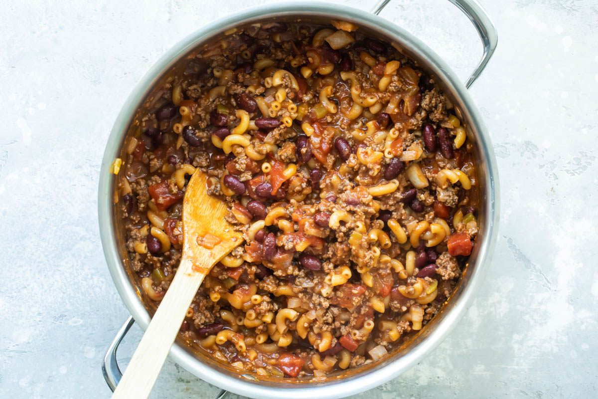 Chili mac in a Dutch oven with a wooden spoon resting in it.