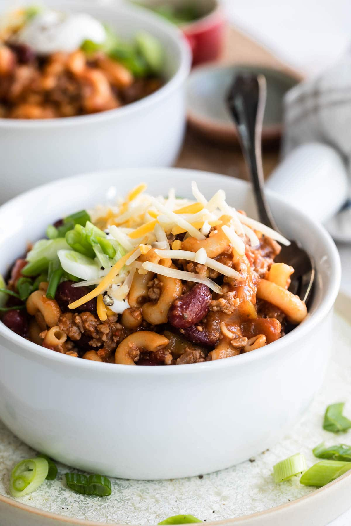 Garnished chili mac in a white handled bowl.