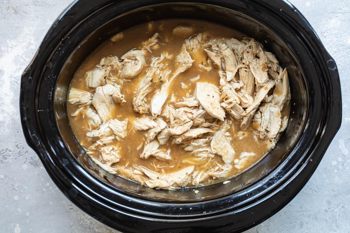 Hot turkey sandwich meat shredded in a slow cooker.