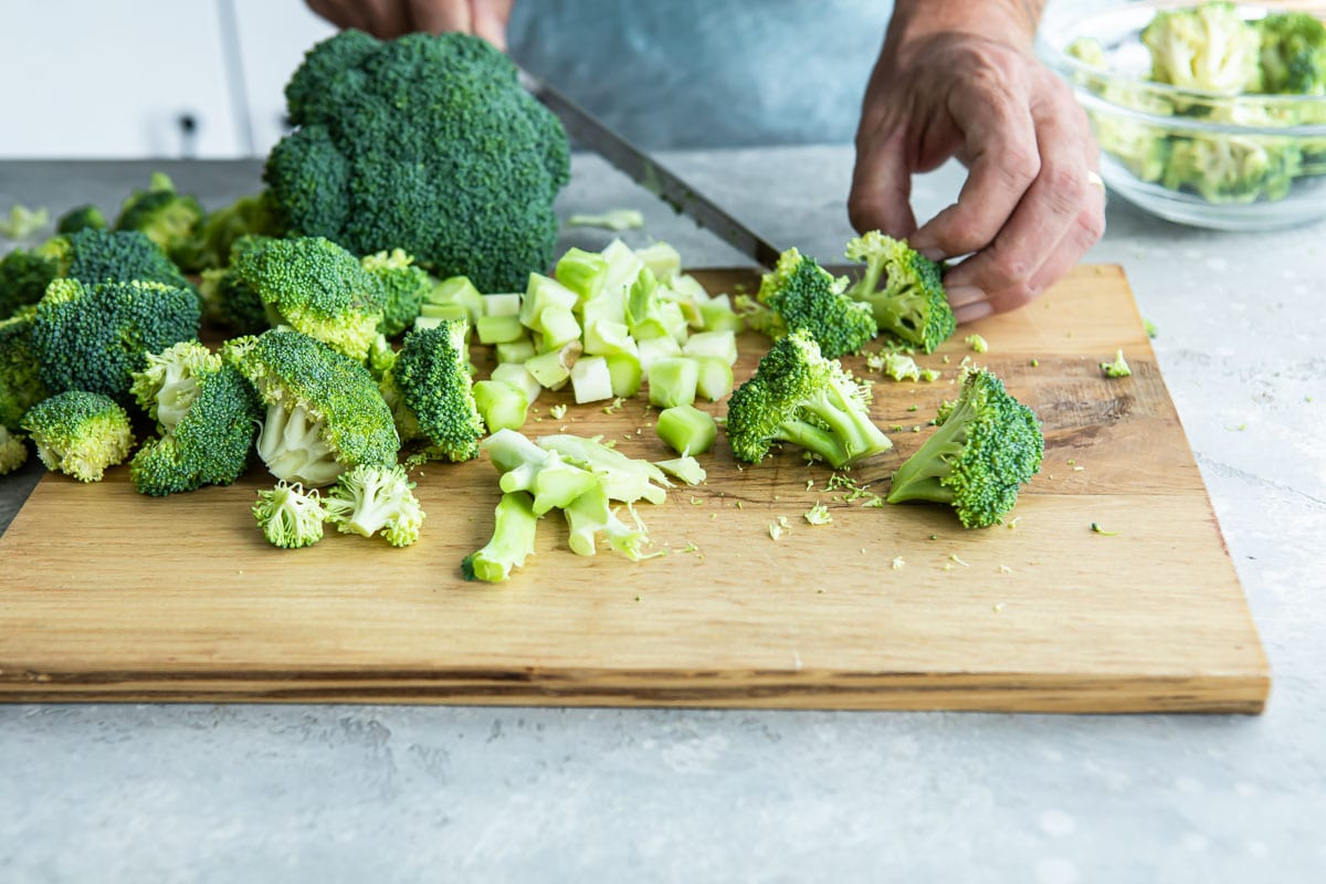 Cut up broccoli on a cutting board.