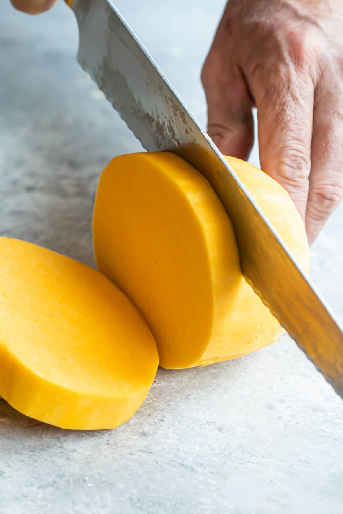Peeled butternut squash being sliced into rounds.