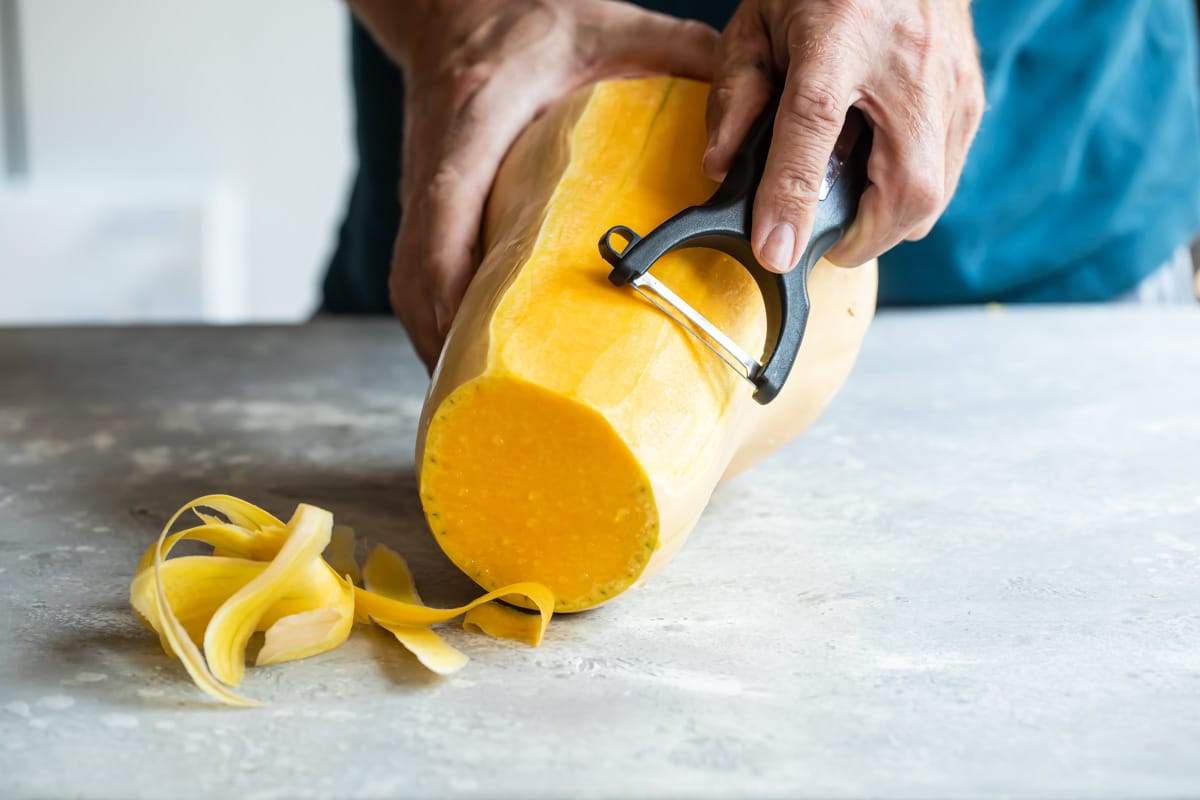 Peeling butternut squash with a vegetable peeler.