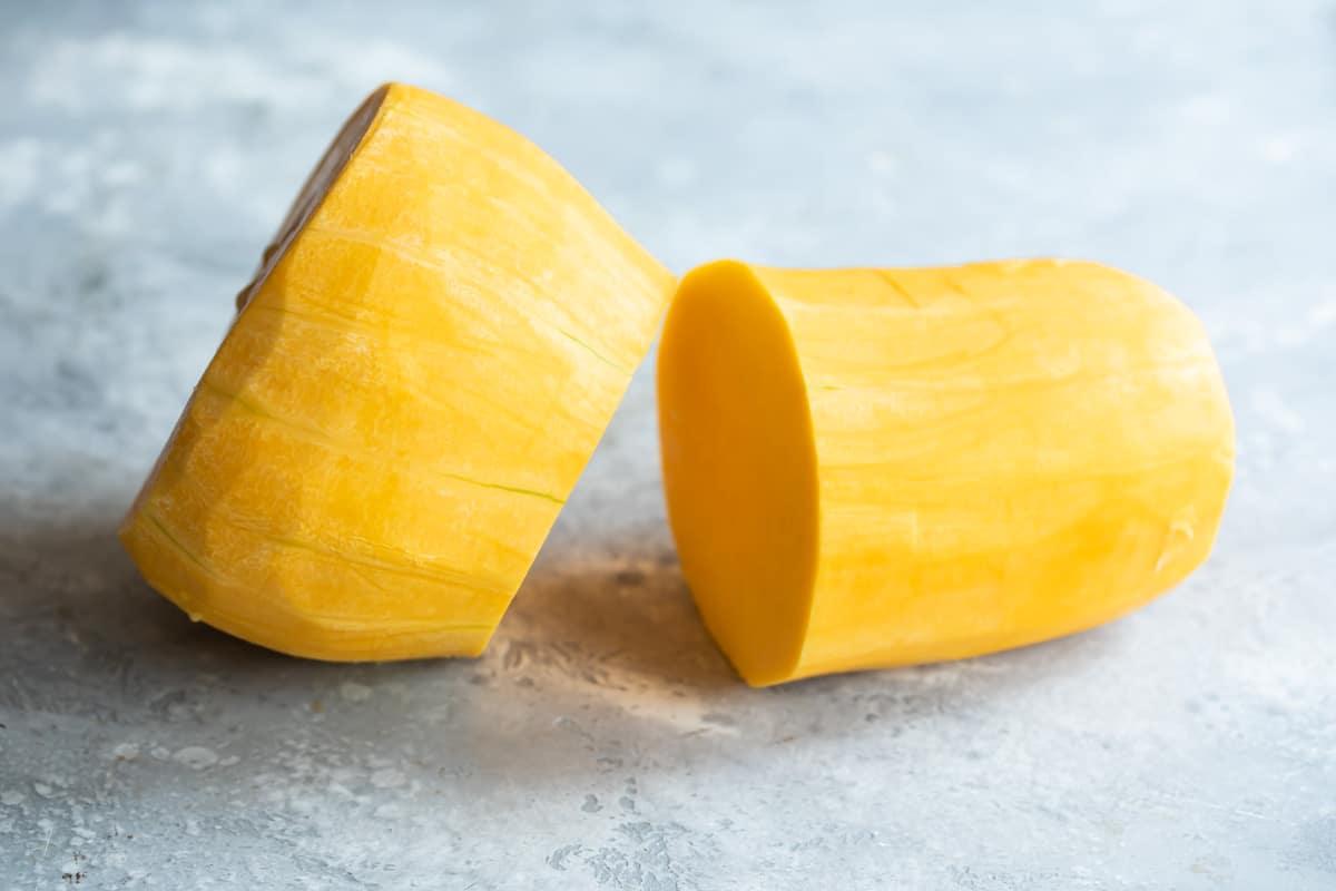 Peeled butternut squash being cut in half.