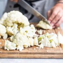Raw cauliflower being chopped on a wooden cutting board.