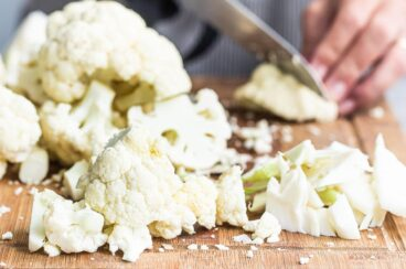 Raw cauliflower being chopped on a wooden cutting board.