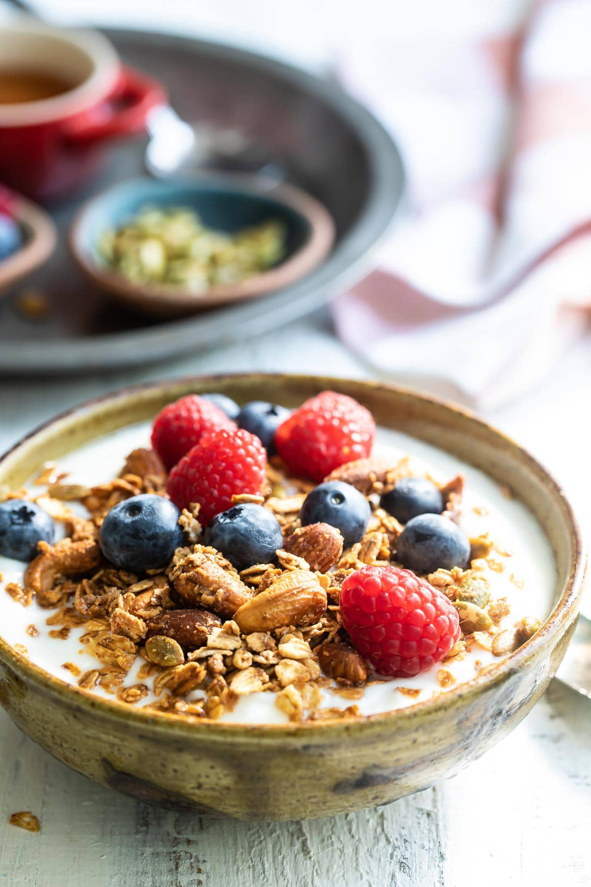 Granola and berries on top of a bowl of yogurt.