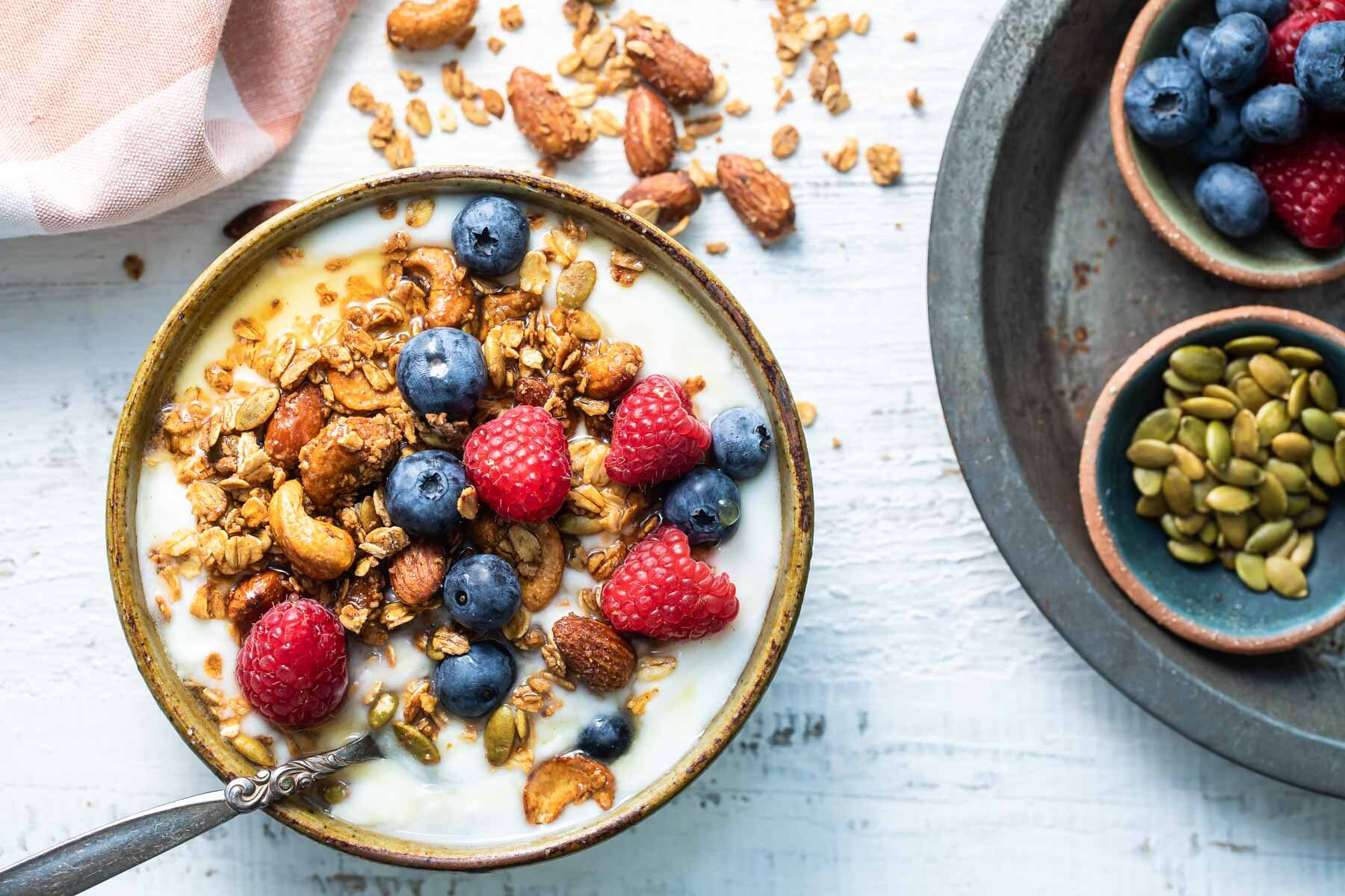 Granola and berries topping a bowl of yogurt.