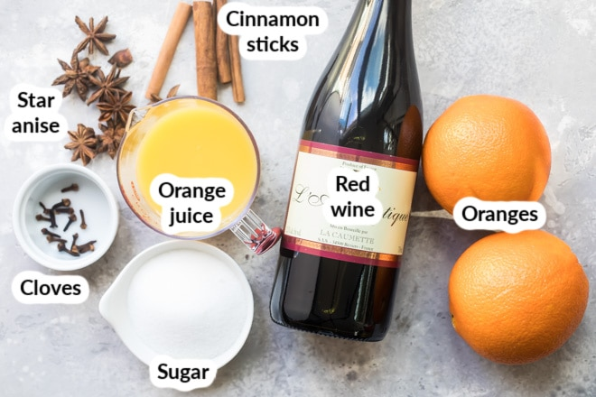 Labeled ingredients for mulled wine in various bowls.