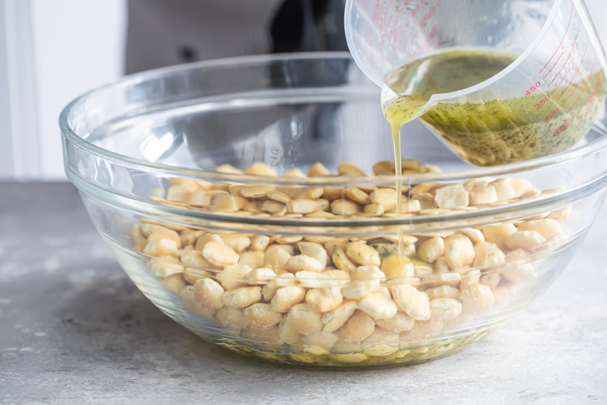 Ranch liquid mixture being poured over oyster crackers in a clear bowl.
