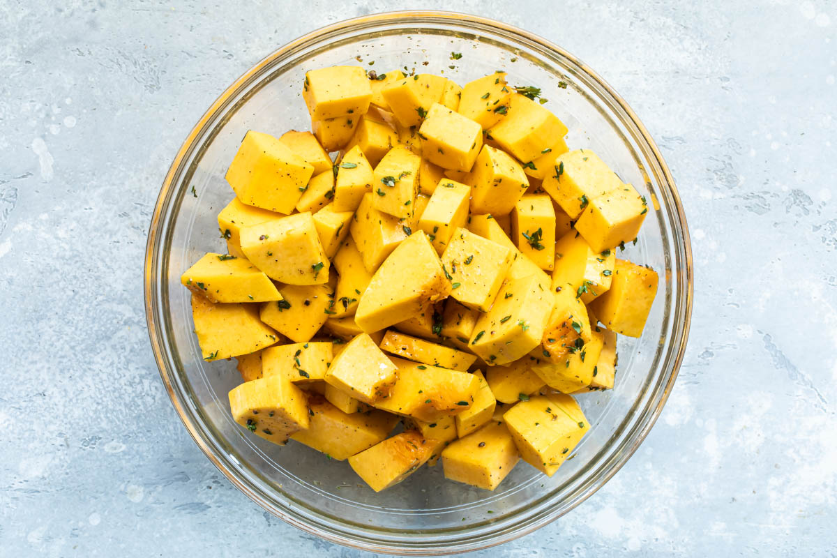 Raw cubed butternut squash in a bowl with olive oil and fresh thyme.