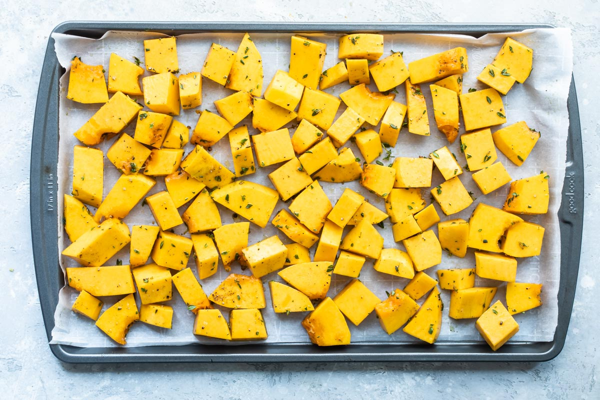 Raw cubed butternut squash on a baking sheet with olive oil and fresh thyme.