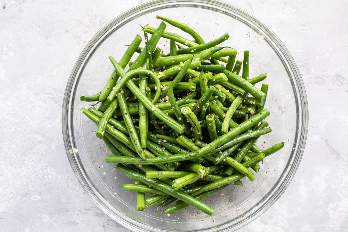 Green beans in a clear bowl coated with oil and seasonings.