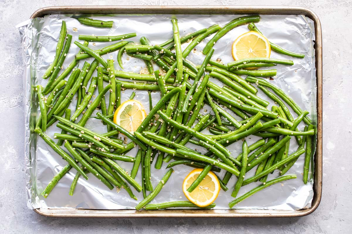 Green beans on a baking sheet coated in oil and seasonings before being roasted.