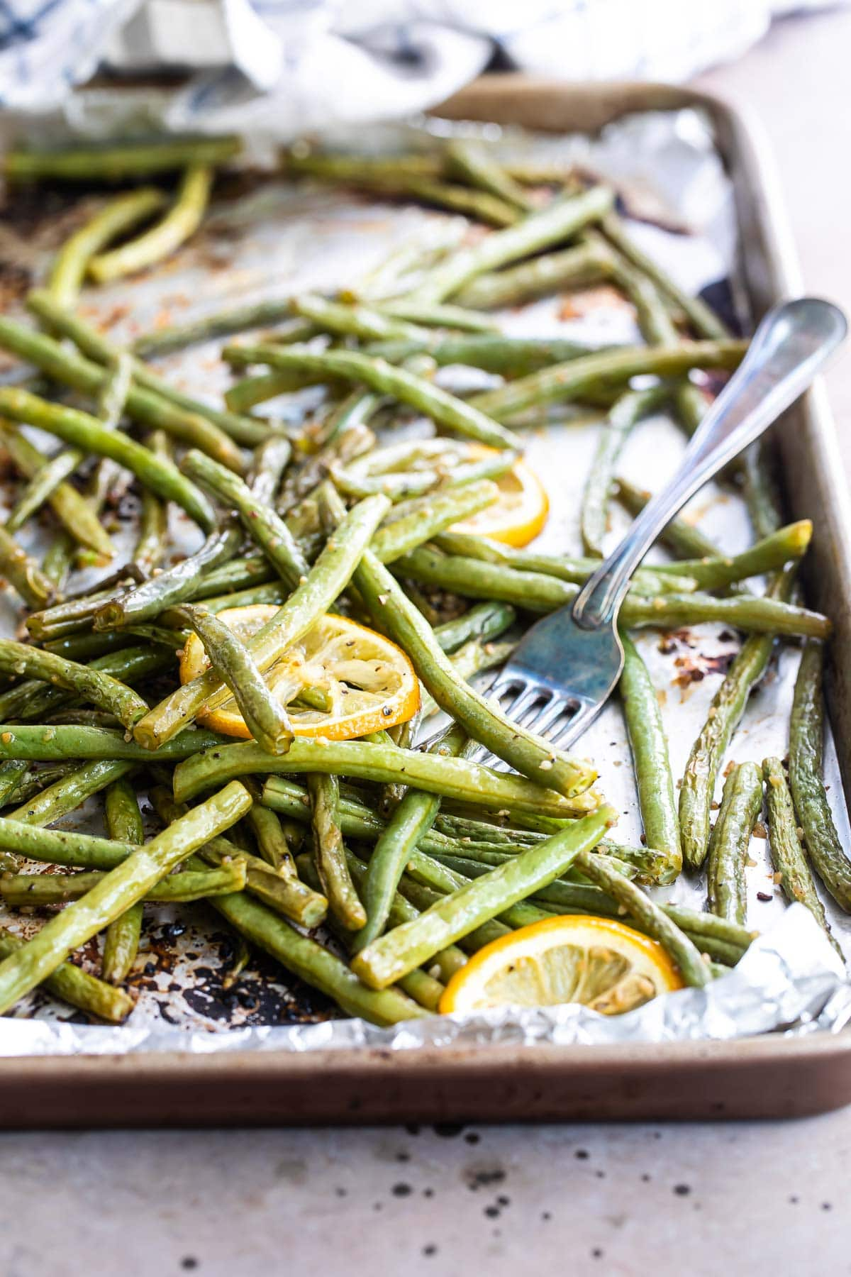 Roasted green beans on a baking sheet with lemon garnish.