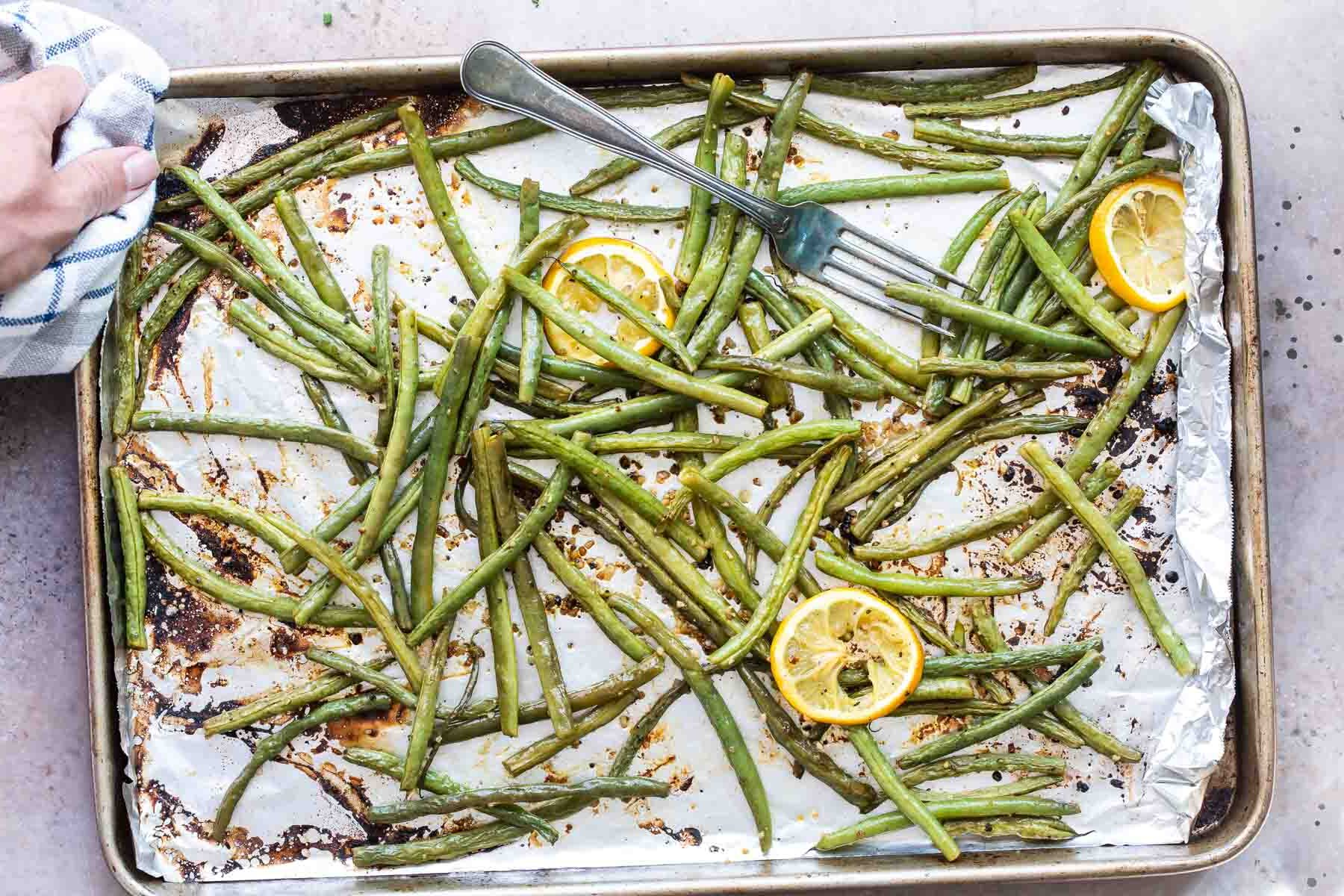 Roasted green beans on a baking sheet with lemon garnish.