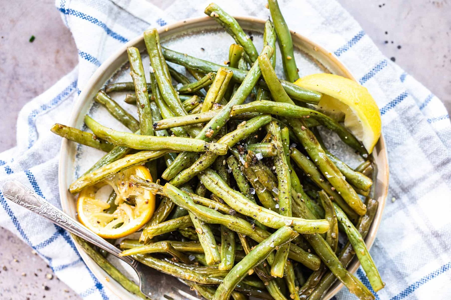 Roasted green beans on a round platter with lemon garnish.