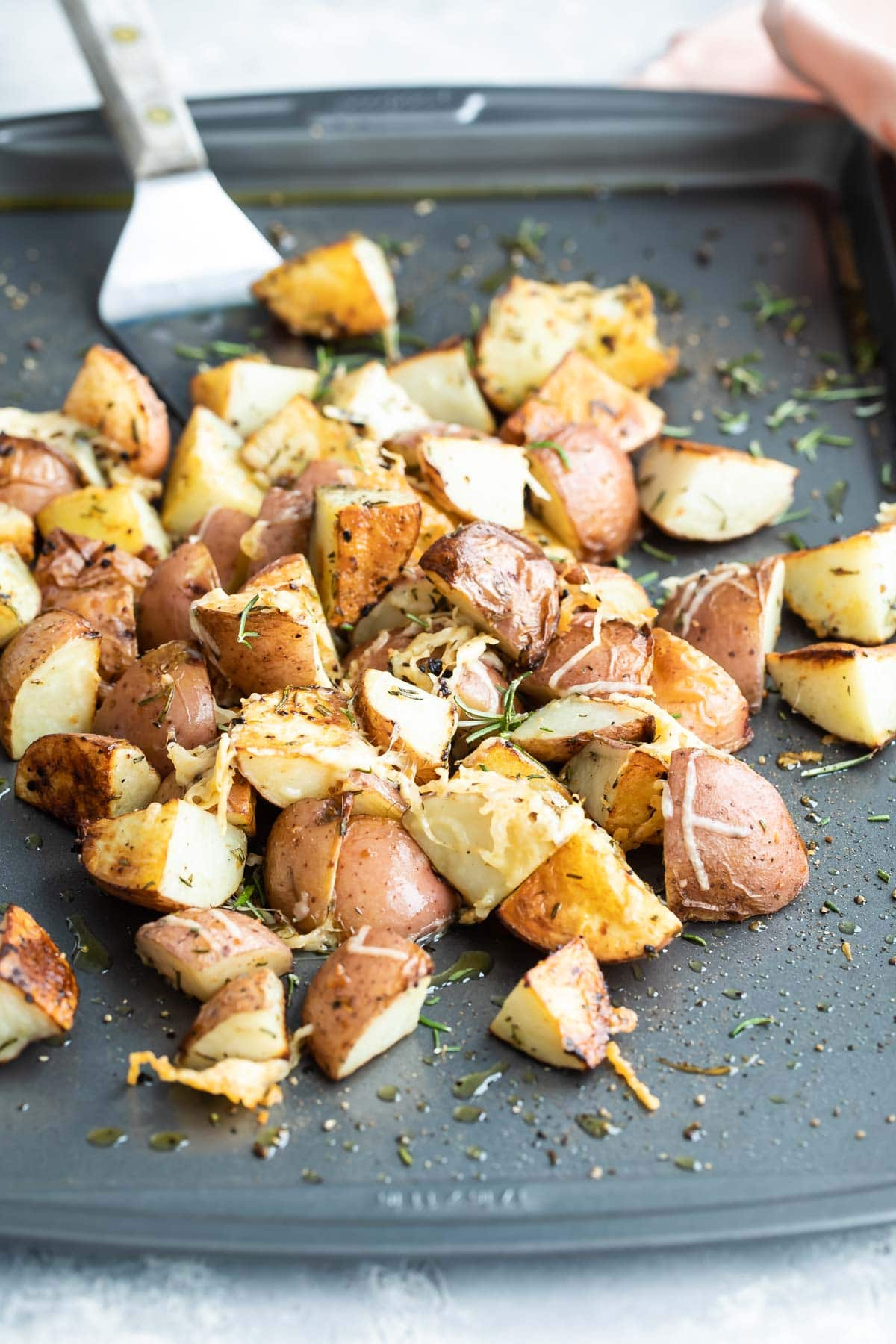 Roasted rosemary potatoes on a silver baking sheet.