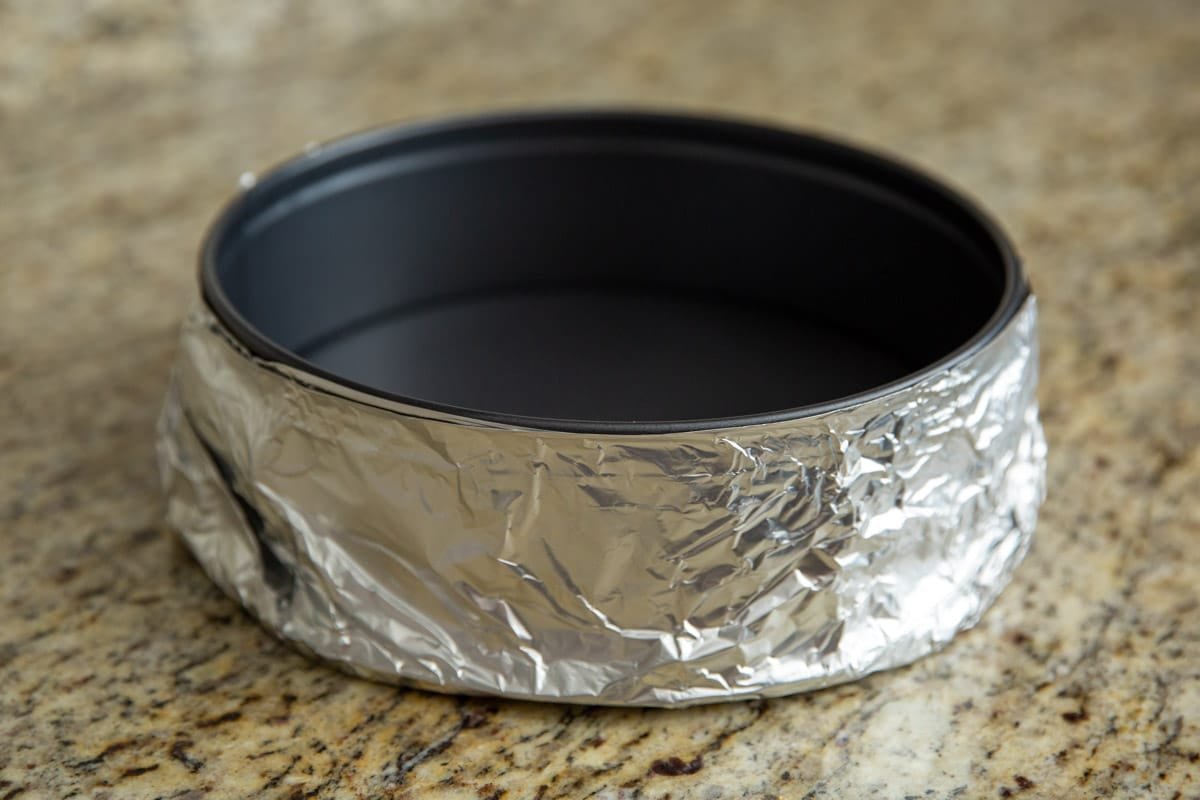 A water bath for a cheesecake with foil wrapped around it.