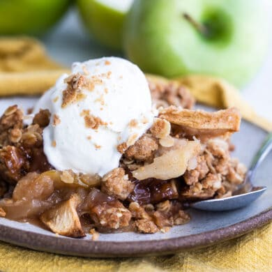Apple crisp on a plate with a scoop of ice cream on top.