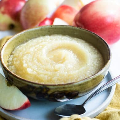A bowl of applesauce with apples behind it.