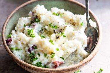 Boursin mashed potatoes in a light green bowl.