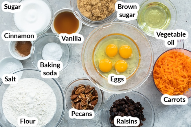 Labeled carrot cake ingredients in various bowls.