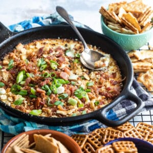 Cheesy bacon dip in a cast iron skillet surrounded by pretzels and crackers.