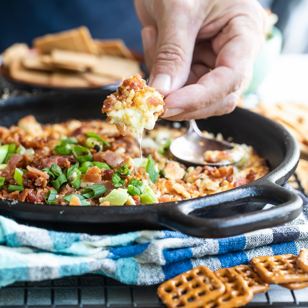 Cheesy bacon dip being scooped out of a cast iron skillet.