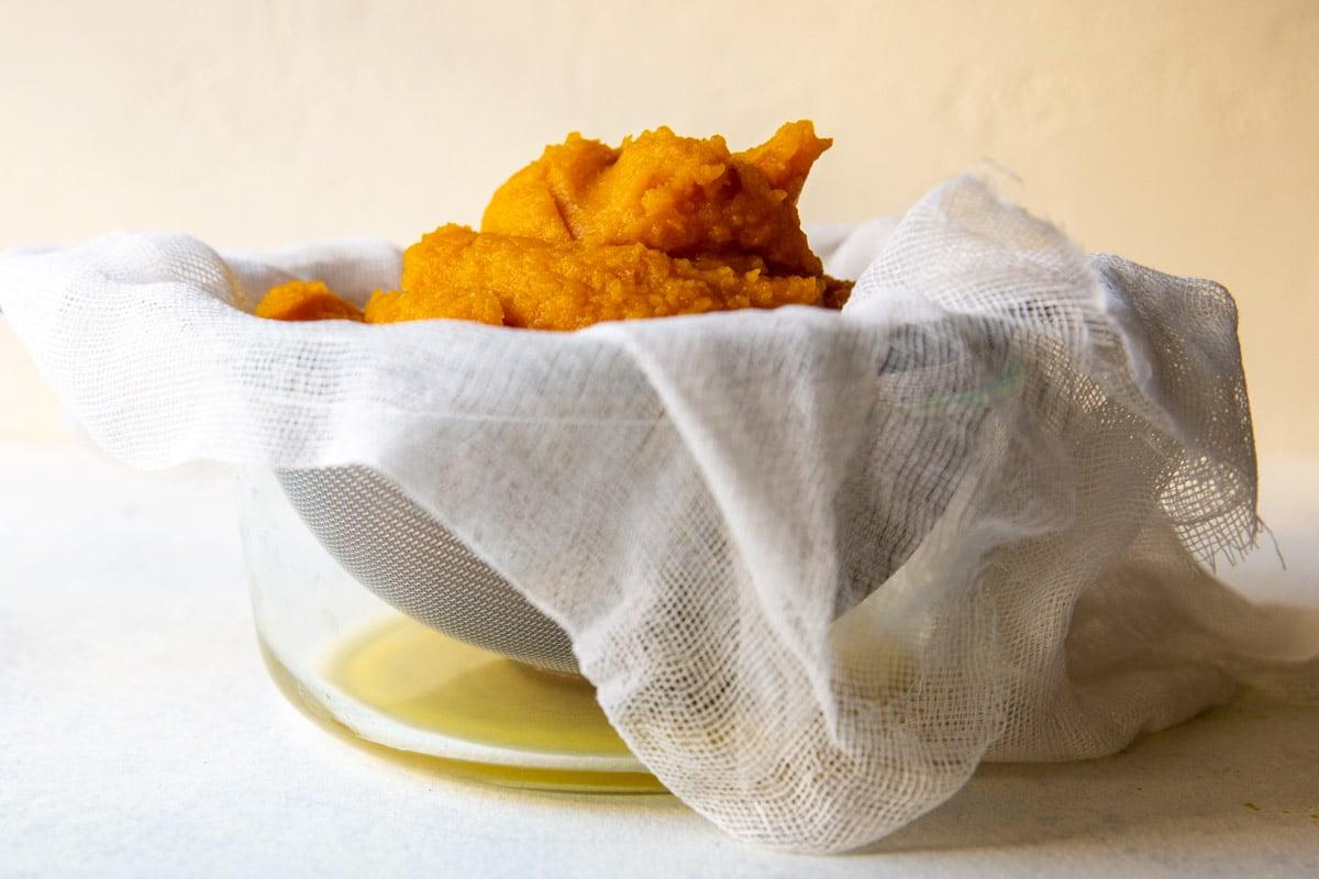 Fresh pumpkin puree draining in cheesecloth.