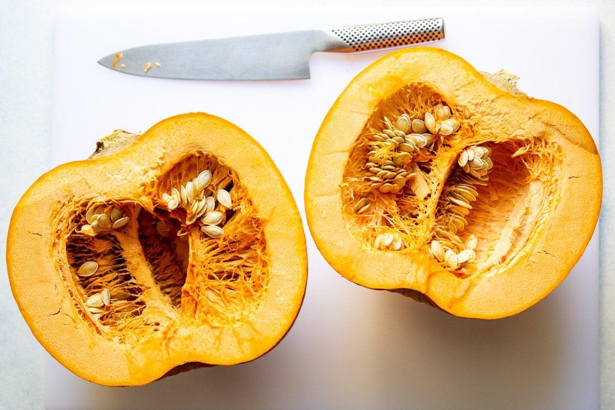 A pumpkin cut in half on a cutting board.