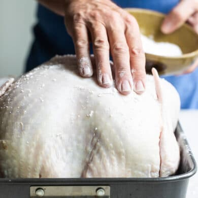 A raw turkey with salt rubbed on it for briniing.