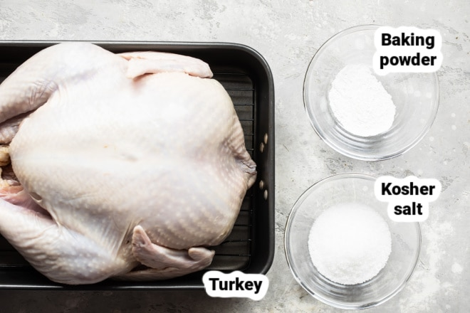 A raw turkey next to bowls of baking powder and salt.