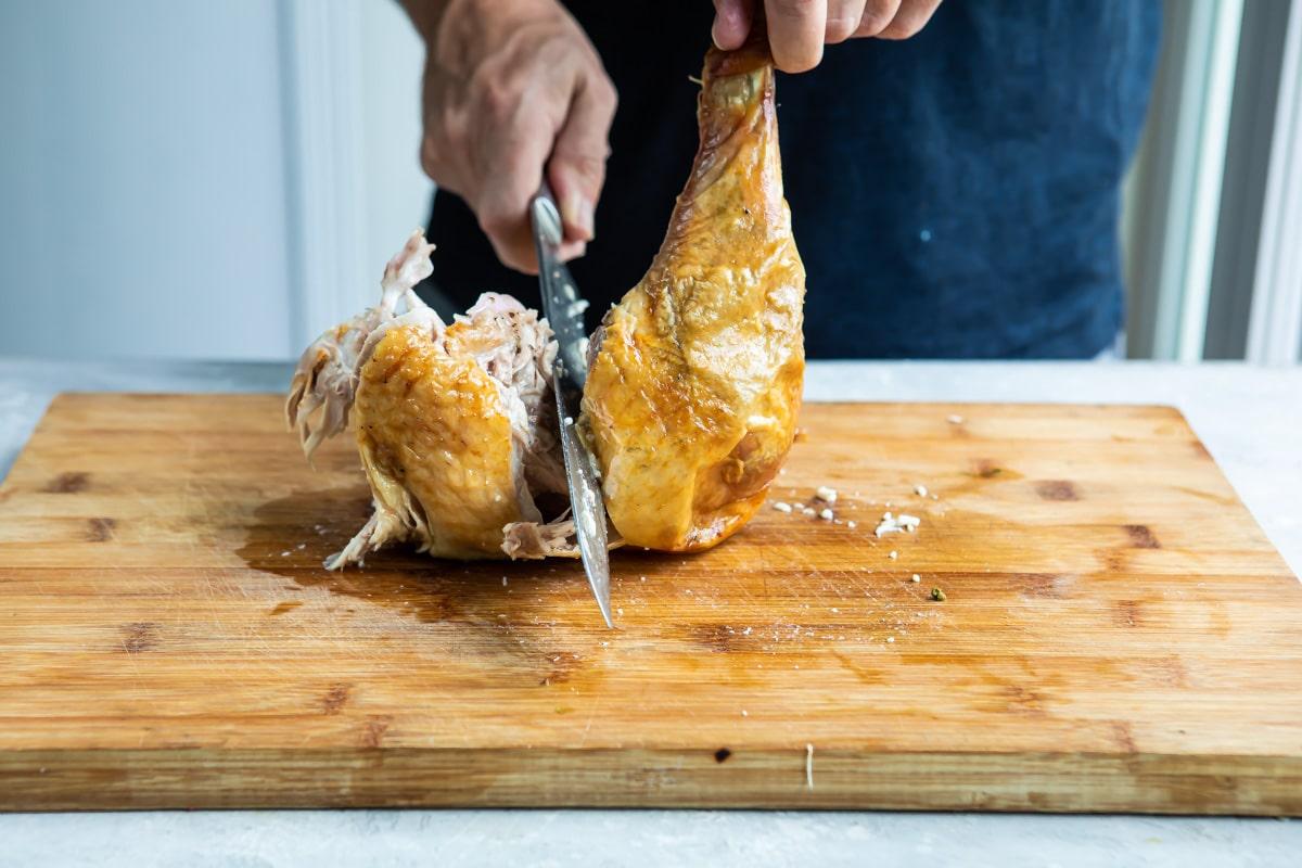 Carving a roasting turkey leg.